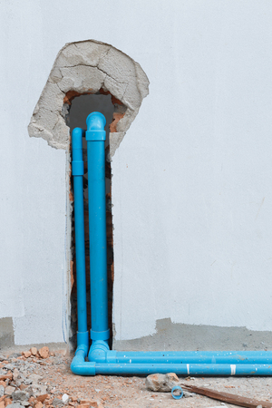 water pipe pvc plumbing under cement wall in construction site building Stock Photo