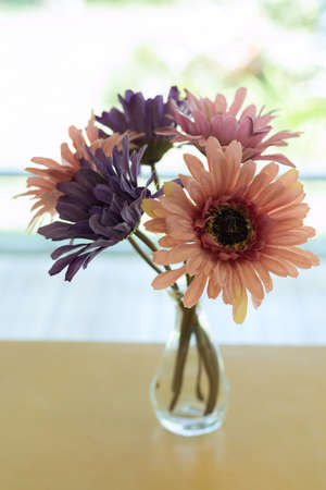 Beautiful Artificial Flower In Small Glass Vase Put On Wood Table