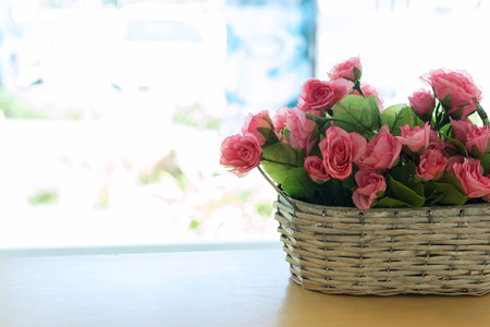 beautiful bouquet rose pink flower artificial in basket put on wood table Stock Photo