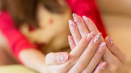 chic: beautiful pink fingernail manicure acrylic nail polish of woman hand beauty fashion