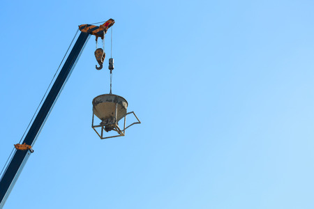 machinery crane hoisting cement mortar mixer bucket container in construction site building industry Stok Fotoğraf