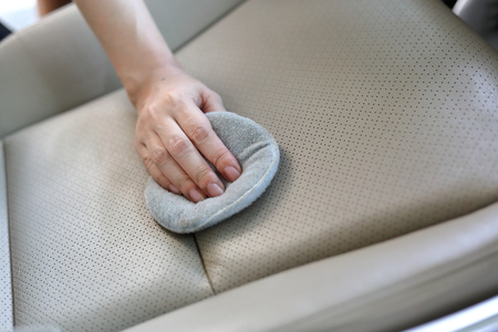 restored: woman hand cleaning leather seat with soft fabric sponge waxing polished, car wash