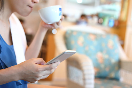 mobile app: freelance business woman using internet mobile phone technology working contact communication in cafe coffee drink