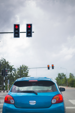 car driving stopped on crossroad with red traffic light