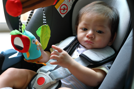 cute baby boy child sitting in car seat with safety belt locked protection Imagens