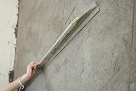 Builder à l'aide de plâtre de lissage à la truelle sur mur de construction