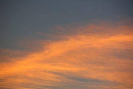 evening clear blue sky with orange sunlight shine through cloud Фото со стока