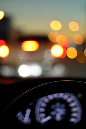 drive vehicle car travel road trip at city night with traffic light on street, image focus steering wheel and blur bokeh abstract background Фото со стока
