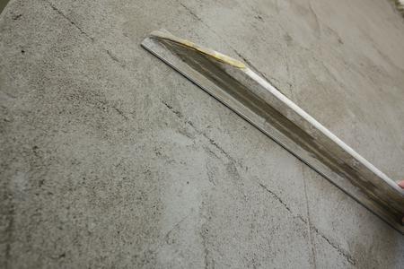 Builder à l'aide de plâtre de lissage à la truelle sur mur de construction Banque d'images