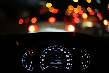 speedometer in modern vehicle car drive travel road trip in night city with blur bokeh traffic light on street background Banco de Imagens