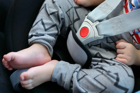 baby sitting in car seat with life safety belt lock protection