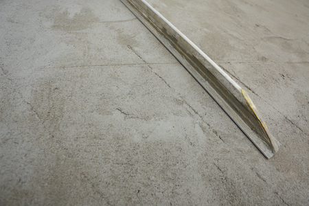 builder using trowel smoothing plaster on construction floor