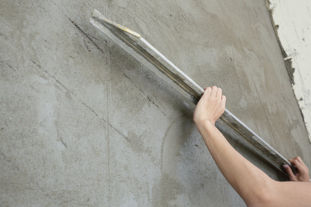 builder using trowel smoothing plaster on construction wall