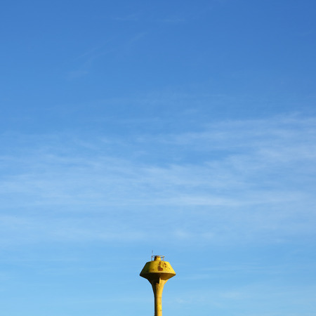 minimal image, yellow water tank with clear blue sky background