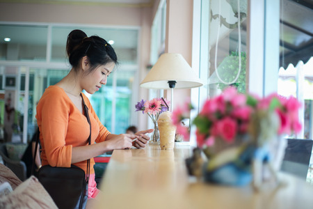 asian woman using mobile in coffee cafe