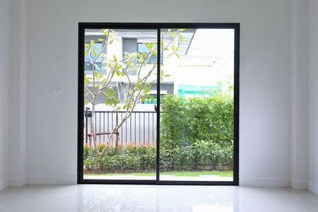 slide glass door with small garden landscaping in front of a new house