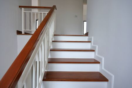 brown wooden stair with white steel balustrade and hardwood handrail banister in modern residential house
