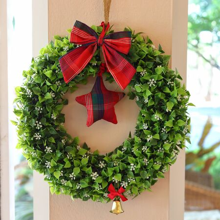 christmas wreath with red bow and star, symbol of xmas holiday celebration ornament decoration in home Stock Photo