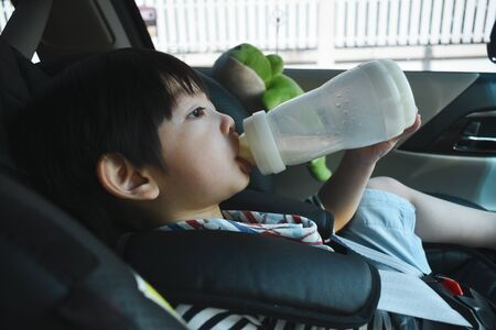 baby boy sucking milk on car seat safety drive Stock Photo