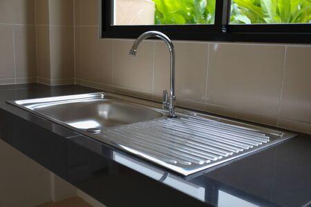 Grifo de agua cerrado y fregadero de acero inoxidable para cocinar en la cocina.
