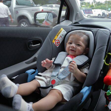 Cute Baby Boy emocionado sentado en el asiento del coche, seguridad, viaje, viaje, viaje por carretera Foto de archivo