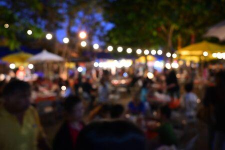 人々は、電球掛け装飾、お祝いの背景に使用される画像ぼかしと屋外ガーデンの夜のパーティーフェスティバルで群がる 写真素材