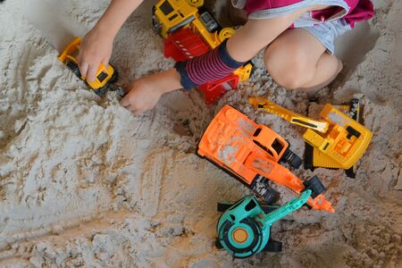 child boy play construction vehicle toy in sand playground