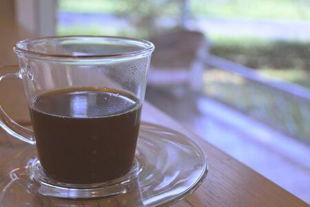 Café negro caliente en vaso puesto sobre la mesa