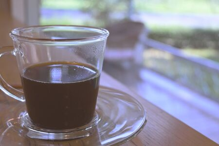 hot black coffee in drinking glass put on table