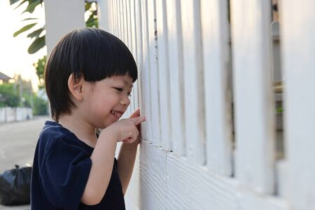 cute boy looking through white wooden front gate of home