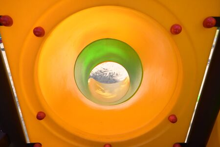 green and yellow in tunnel tube of slide in sand playground Фото со стока