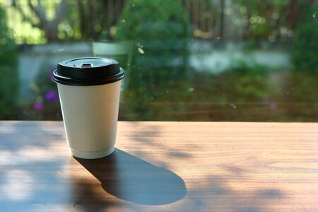 take away cup for hot coffee drink put on wooden table in cafe with sunlight in the morning day shine through the window