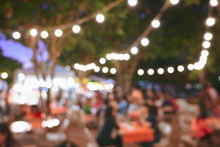 Menschen drängen sich im Nachtfest des Gartens im Freien mit hängender Dekoration der Glühbirne, Bildunschärfe für den Feierhintergrund
