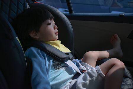 bambino piange seduto sul seggiolino auto guida sicura
