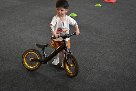 kid playing balance bike in racetrack Stock Photo