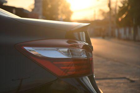 closeup tail light of black modern car in the morning scene