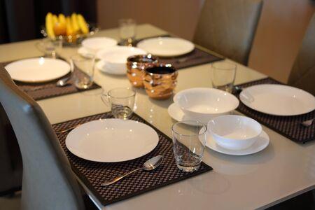white dish ware sets arrange on dinner table inside eating room of modern home interior