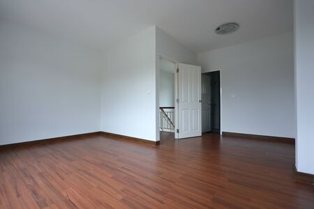 interior design empty room with white wall and wooden laminate floor in new residential house