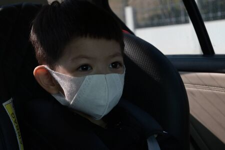 kid sit on car seat wearing hygienic face mask protection care your self from disease spread infection and air pollution