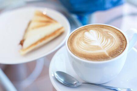 boisson chaude au café au lait et sandwich mis sur la table petit déjeuner le matin