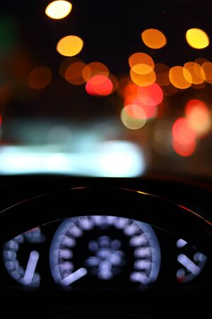 black steering wheel inside car drive in night city street