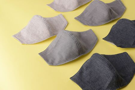 flat lay design of fashion face mask handmade from fabric cloth on yellow background Stockfoto