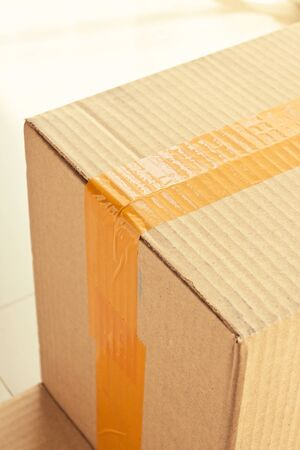 brown carton paper box package with packing scotch tape stick