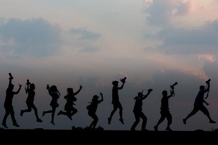 pandilla: El fotógrafo pandilla saltando Silueta Foto de archivo