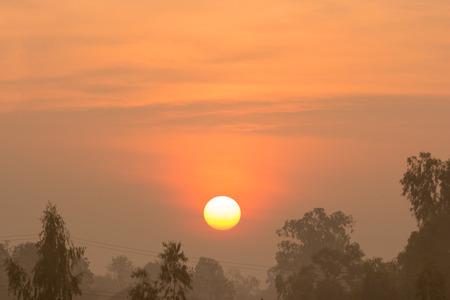 faintly visible: Sunrise and trees on farm Stock Photo