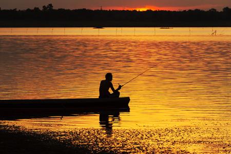 Fishermen fishing on a boat silhouette. Stok Fotoğraf