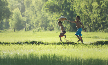 Action two children running on the berms, ditches in fields. playfully The life of children a farmer in Thailand. 写真素材