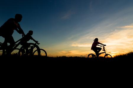 silueta ciclista: Ejercicio en bicicleta Familia durante el atardecer. Foto de archivo