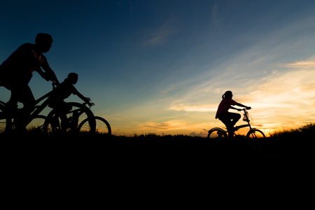 cycling silhouette: Family cycling exercise during sunset. Stock Photo