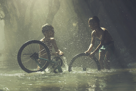 wean: The boys playing with bicycle water splash on creek.